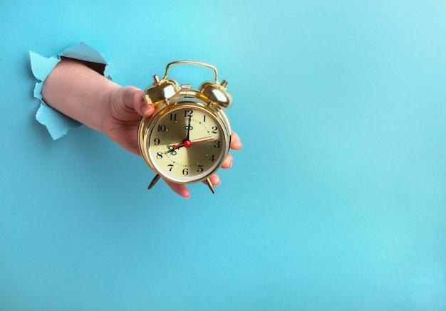 Despertador em uma mão feminina sobre um fundo azul com um buraco, conceito de tempo