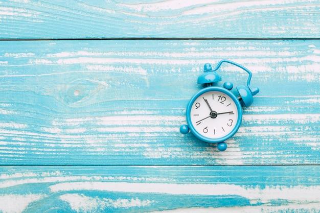 Despertador em uma mesa de madeira azul
