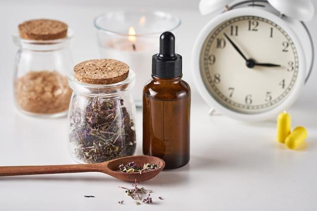 Despertador, ervas medicinais e óleo de aromaterapia em fundo branco