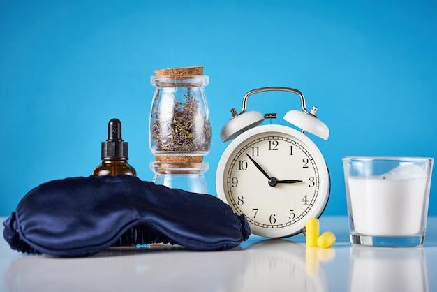 Despertador, ervas medicinais e óleo de aromaterapia em um azul