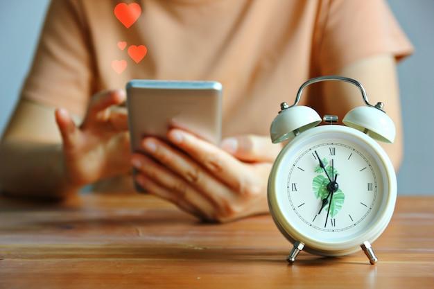 Despertador estilo vintage na frente de uma mulher usando o celular para enviar emoção de amor Foto Premium