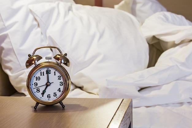 Despertador fica em uma mesa de cabeceira no quarto