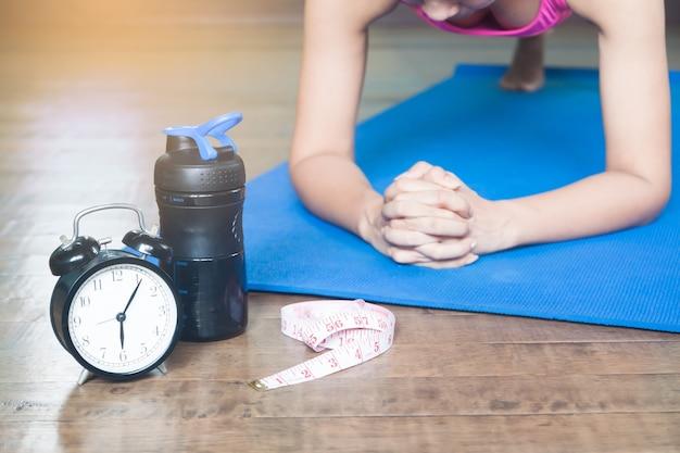 Despertador, fita métrica e mulher yoga asiática em casa, fundo de trabalho e conceito de estilo de vida, foco seletivo