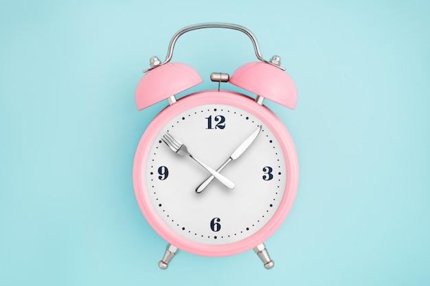Despertador. garfo e faca em vez de ponteiros do relógio. conceito de jejum intermitente, hora do almoço, dieta e perda de peso