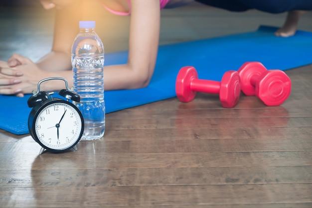 Despertador, garrafa de água, halteres e mulher asiática yoga em casa no fundo, conceito de exercício e estilo de vida, foco seletivo