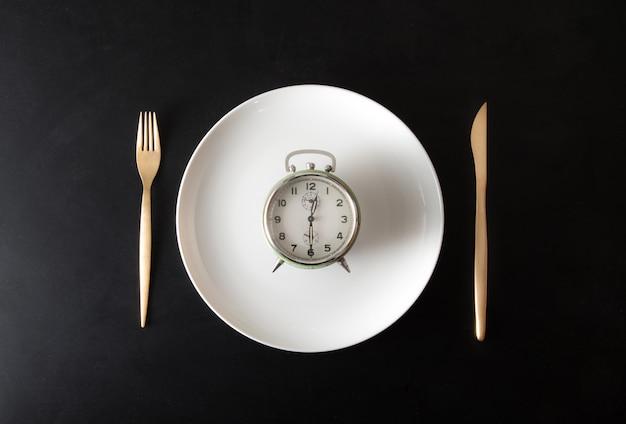 Despertador isolado no prato no escuro