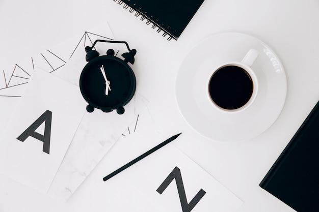 Despertador; lápis; diário; xícara de café e papel com letra ae no pano de fundo branco