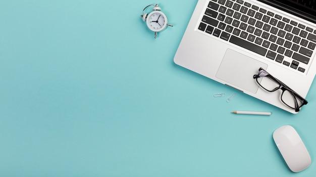 Despertador, lápis, óculos, laptop, mouse na mesa de escritório azul