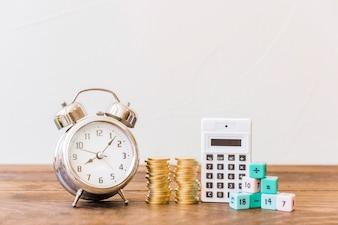 Despertador, moedas empilhadas, calculadora e blocos de matemática na mesa de madeira