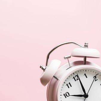 Despertador mostrando o tempo 10'o relógio contra fundo rosa