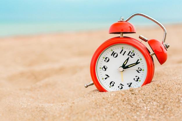 Despertador na areia da praia