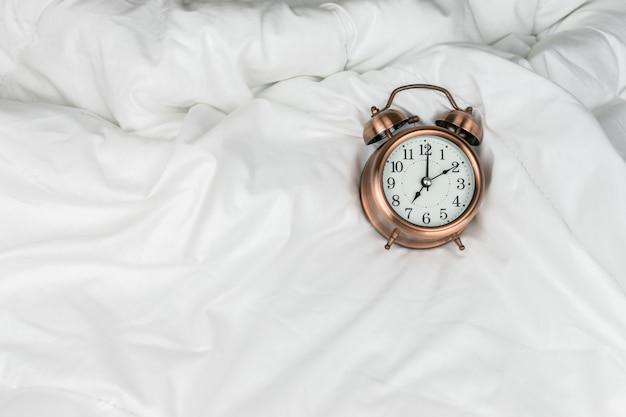 Despertador na cama branca