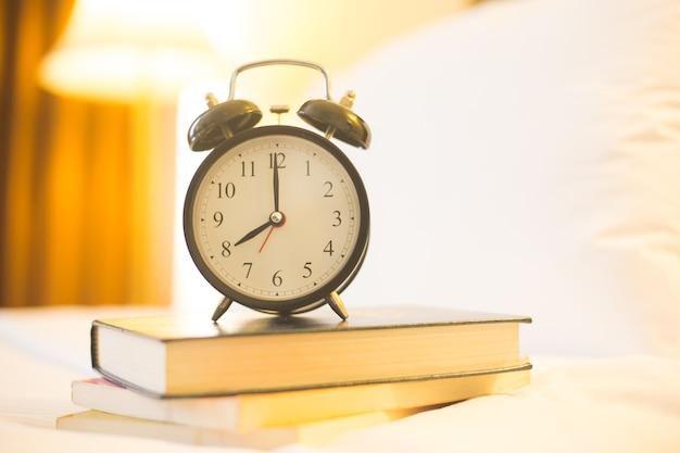 Despertador na cama com o livro no tempo de manhã.