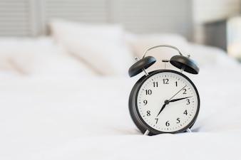 Despertador na cama com roupa de cama branca