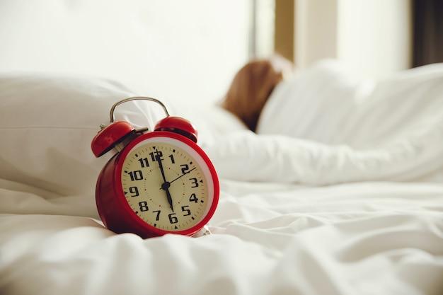 Despertador na cama e mulher dormindo no fundo