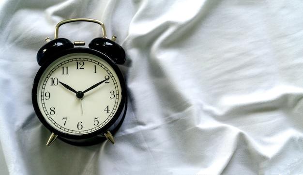 Despertador na cama no quarto do hotel de manhã