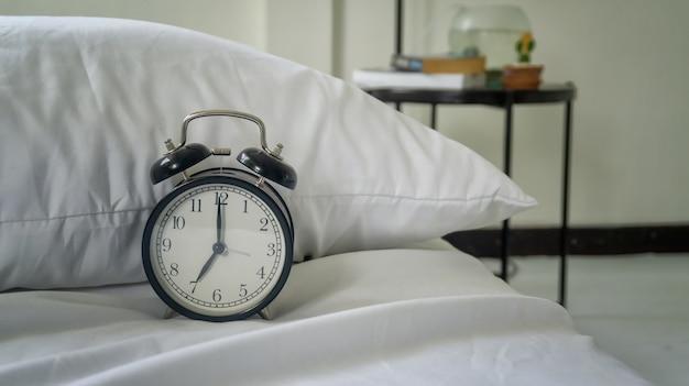 Despertador na cama no quarto do hotel e fundo travesseiro