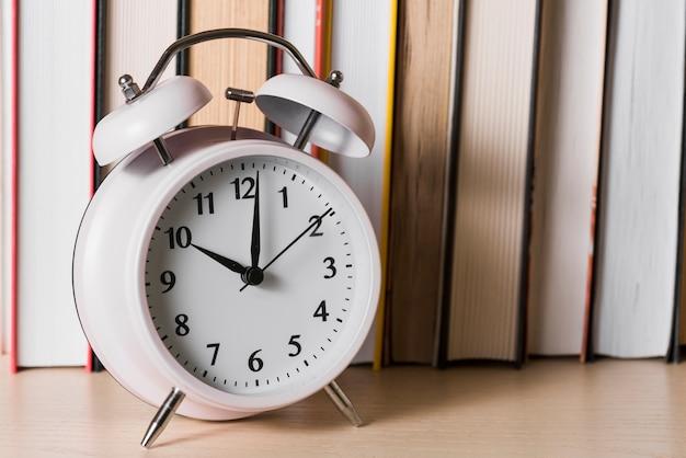 Despertador na frente da estante na mesa de madeira