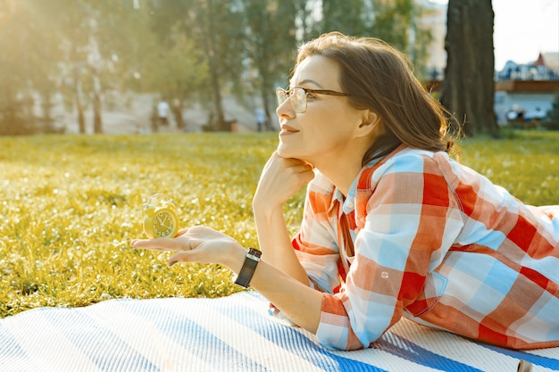 Despertador na mão fêmea, grama verde no parque, luz solar, espaço da cópia, hora dourada.