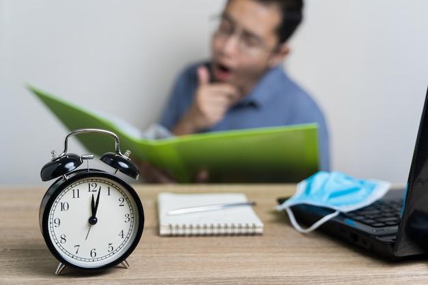 Despertador na mesa à meia-noite com empresário embaçado trabalhando