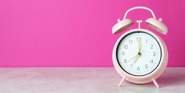 Despertador na mesa branca contra rosa