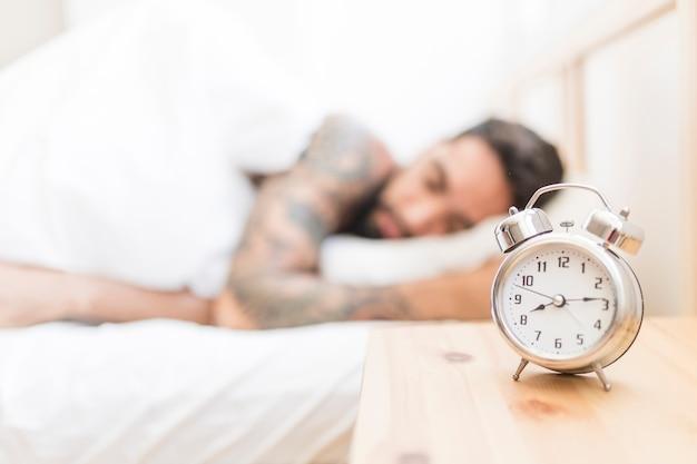 Despertador na mesa de madeira com homem dormindo no fundo