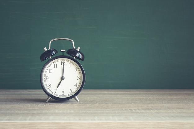 Despertador na mesa de madeira no fundo do quadro-negro em sala de aula