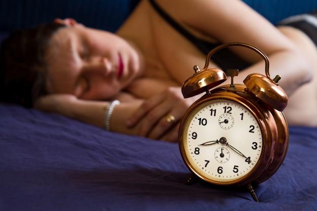 Despertador na mesa e mulher dormindo
