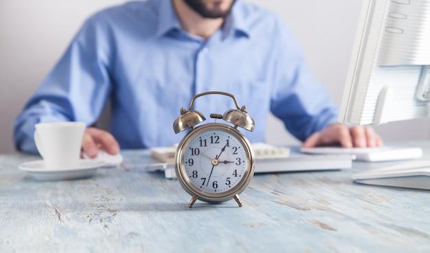 Despertador na mesa. empresário trabalhando no escritório