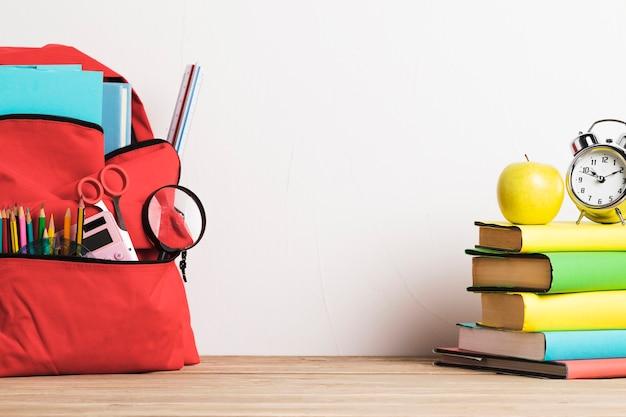 Despertador na pilha de livros e mochila escolar bem embalada com suprimentos