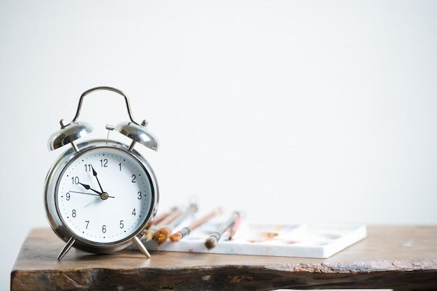 Despertador na tabela de madeira com a escova de pintura no fundo branco da parede.