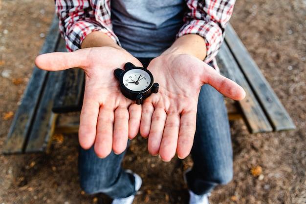 Despertador nas mãos de um homem irreconhecível, sentado em um parque.