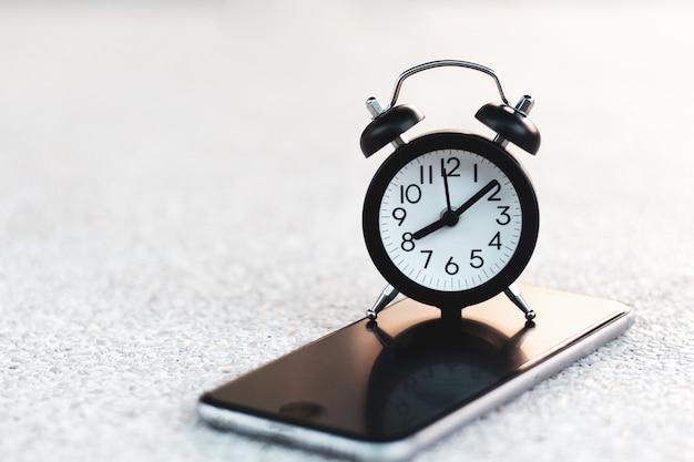 Despertador no telefone esperto móvel com espaço da cópia.