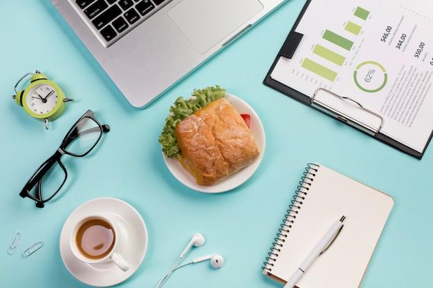 Despertador, óculos, café da manhã, fones de ouvido, blocos de notas em espiral e orçamento plano na prancheta contra o pano de fundo azul
