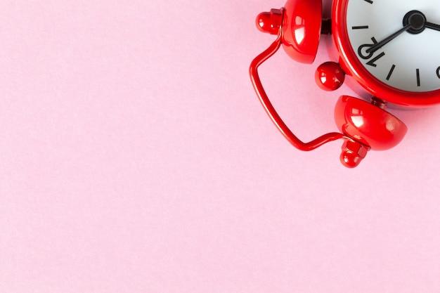 Despertador pequeno vermelho no fundo claro do rosa pastel com copyspace.