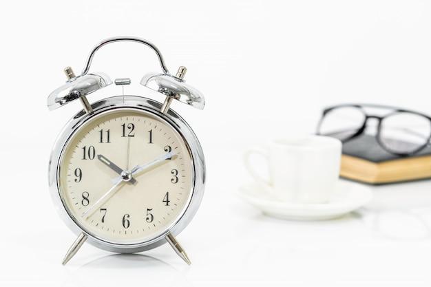 Despertador prata, xícara de café, óculos e um livro antigo