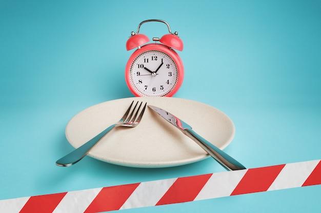 Despertador, prato com talheres e fita de barreira.