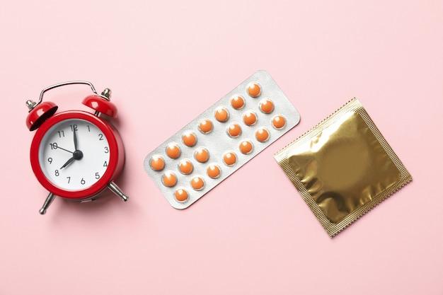 Despertador, preservativo e comprimidos em fundo rosa