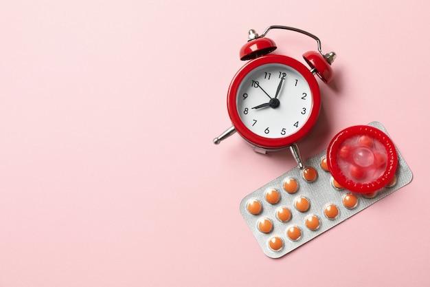 Despertador, preservativo e comprimidos na superfície rosa