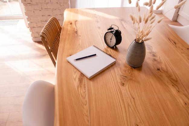 Despertador preto, bloco de notas e estacionário em uma mesa de madeira.