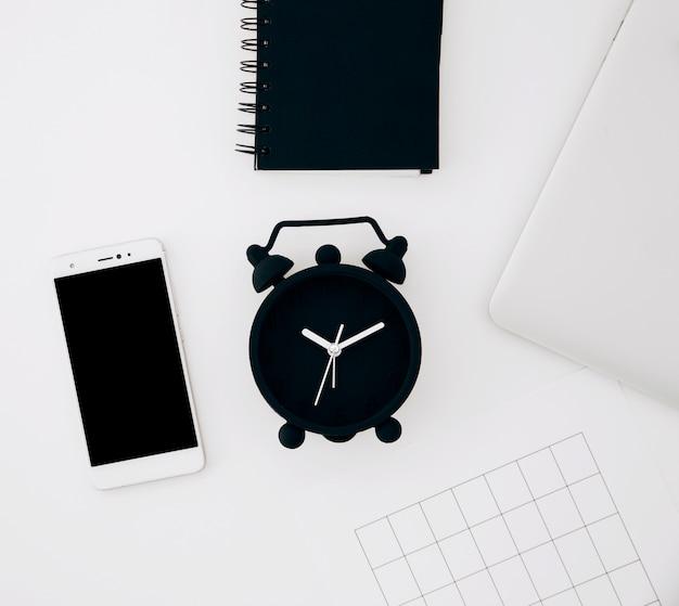Despertador preto; bloco de notas em espiral; smartphone; página e laptop na mesa branca