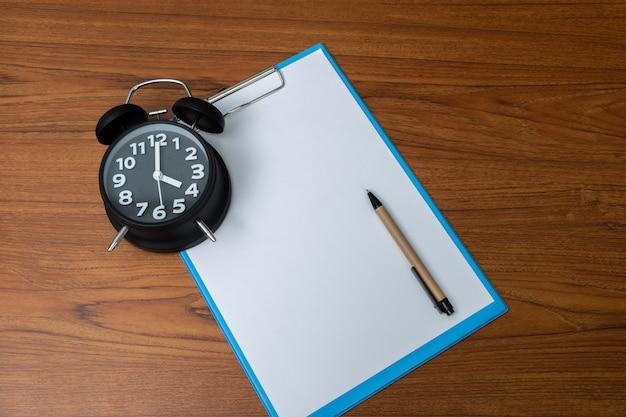Despertador preto com prancheta e papel branco e caneta