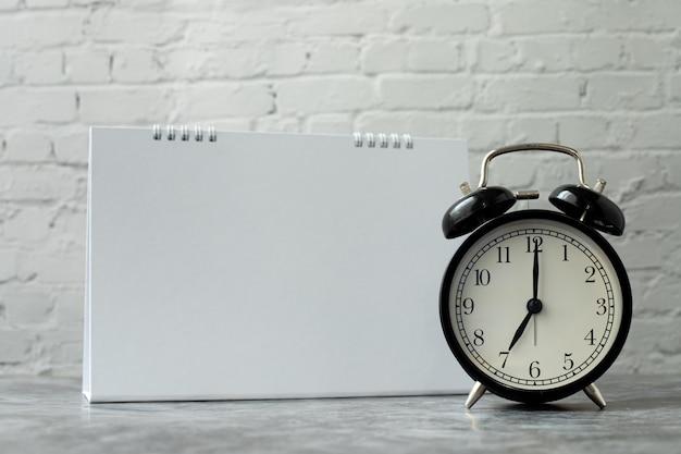 Despertador preto com tela em branco no calendário.
