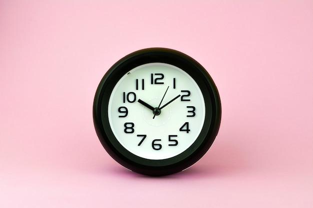 Despertador preto e branco no fundo cor-de-rosa.