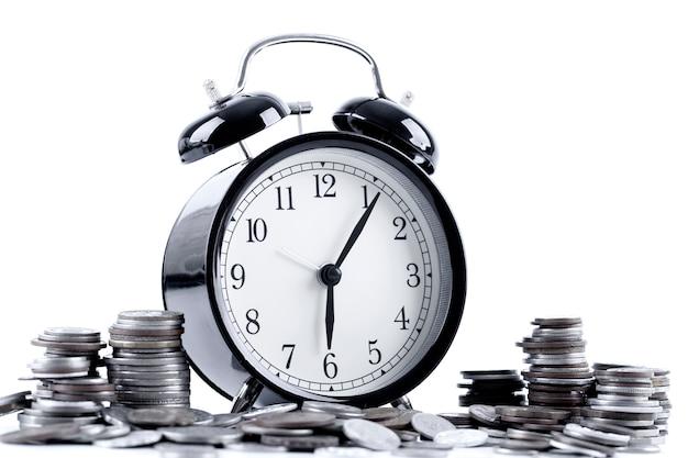 Despertador preto e pilha de moedas para a hora do conceito do negócio e da finança.