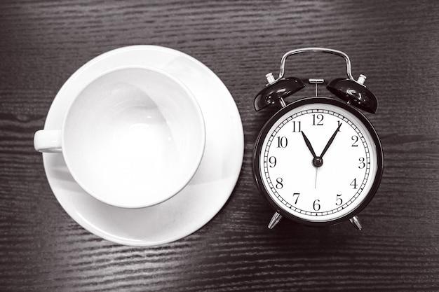 Despertador preto está em uma mesa de madeira e há uma caneca vazia branca