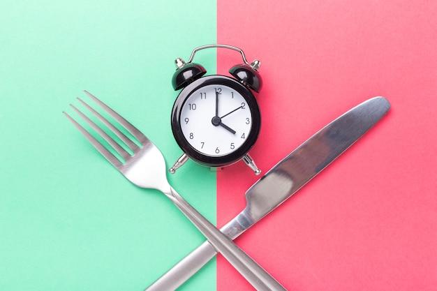 Despertador preto, garfo, faca em fundo de papel colorido. conceito de jejum intermitente - imagem