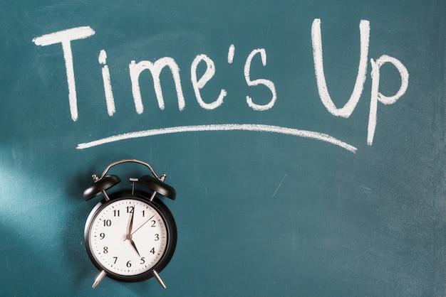 Despertador preto na frente do quadro verde com tempos escritos texto