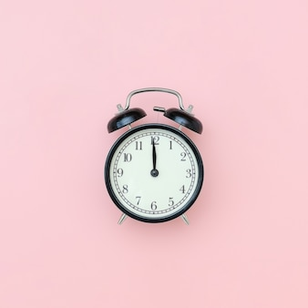 Despertador preto no centro na tabela cor-de-rosa, close up. estilo minimalista copie o espaço vista superior.