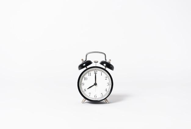 Despertador preto no fundo cinzento. idéia criativa de objeto mínimo.